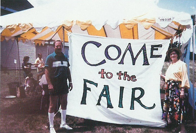 """""""Come to the fair"""" reads a large handmade sign, flanked with smiling people, outside of the sanctuar"""