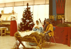 Two youth, dressed as Mary and Joseph, watch over the manger in a Christmas pageant of the 1980s.