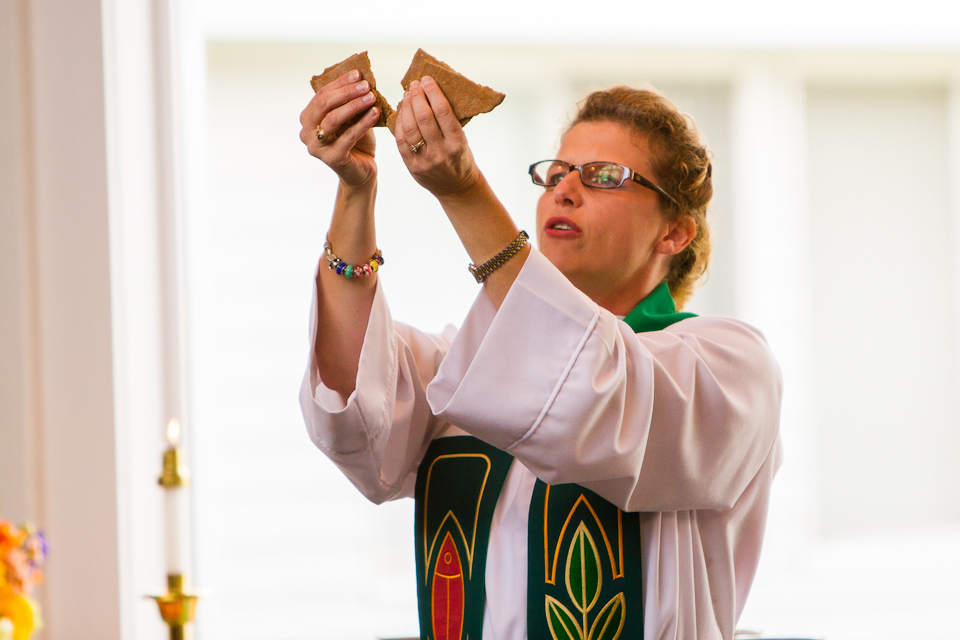 A visiting pastor breaks the communion bread at the altar of Friends Congregational.