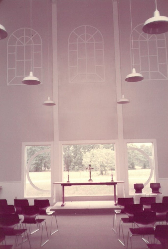 The sanctuary of years past, sparse and clean with plastic chairs empty and ready. Date unknown.