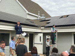 The pastors address the congregational from step ladders as they christen the new solar panels insta