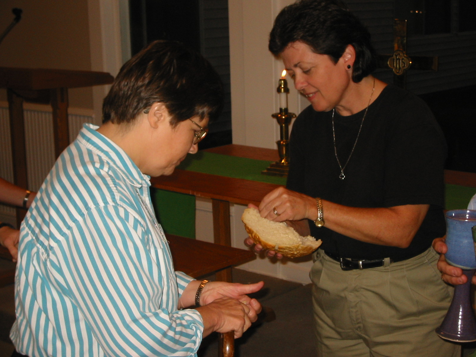 The pastor uses her hands to break off a piece of communion bread for a member of the congregation.