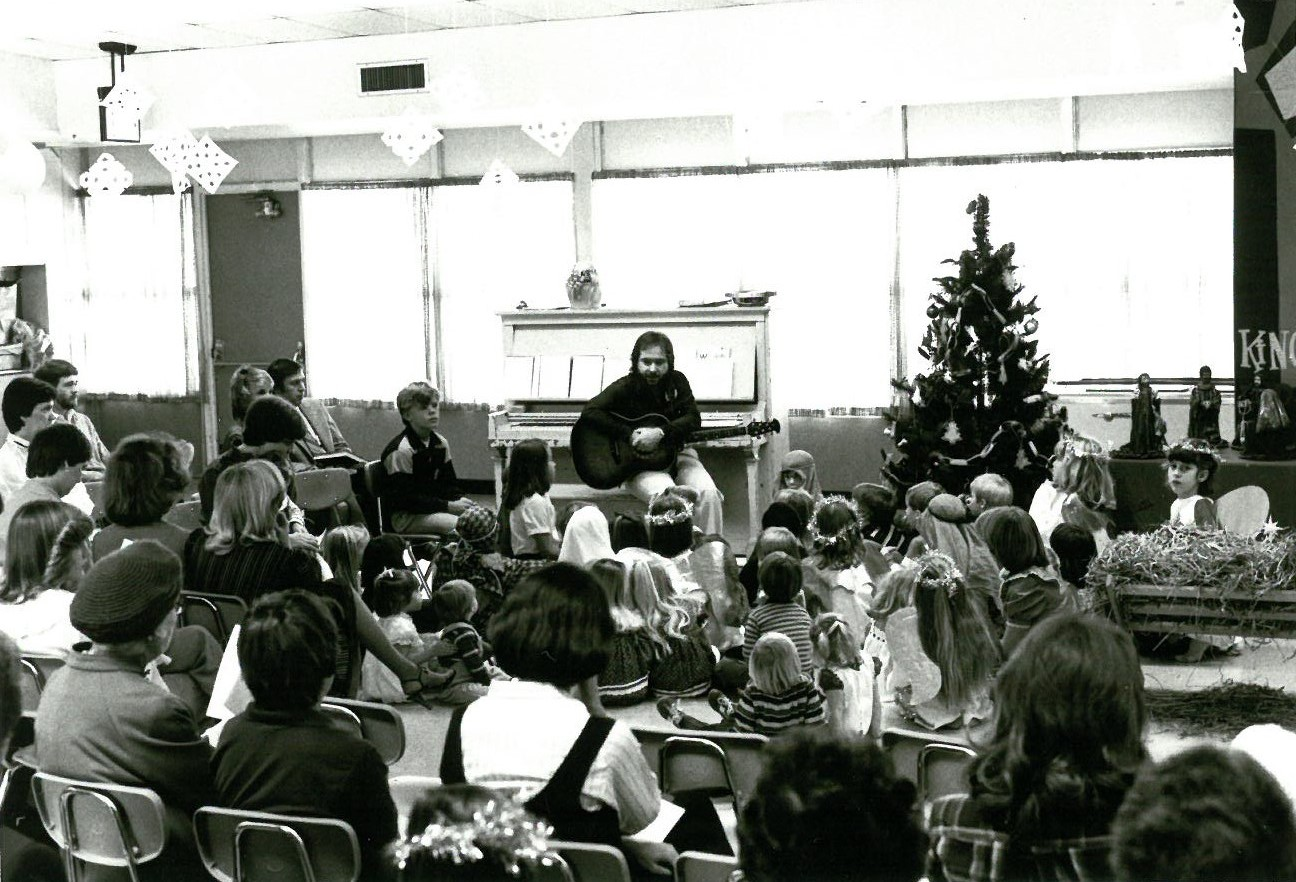 In a black-and-white photo, a man prepares to play guitar for a crowd of children in the sanctuary.