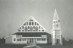 A black-and-white photo shows the original church building, circa 1980s.