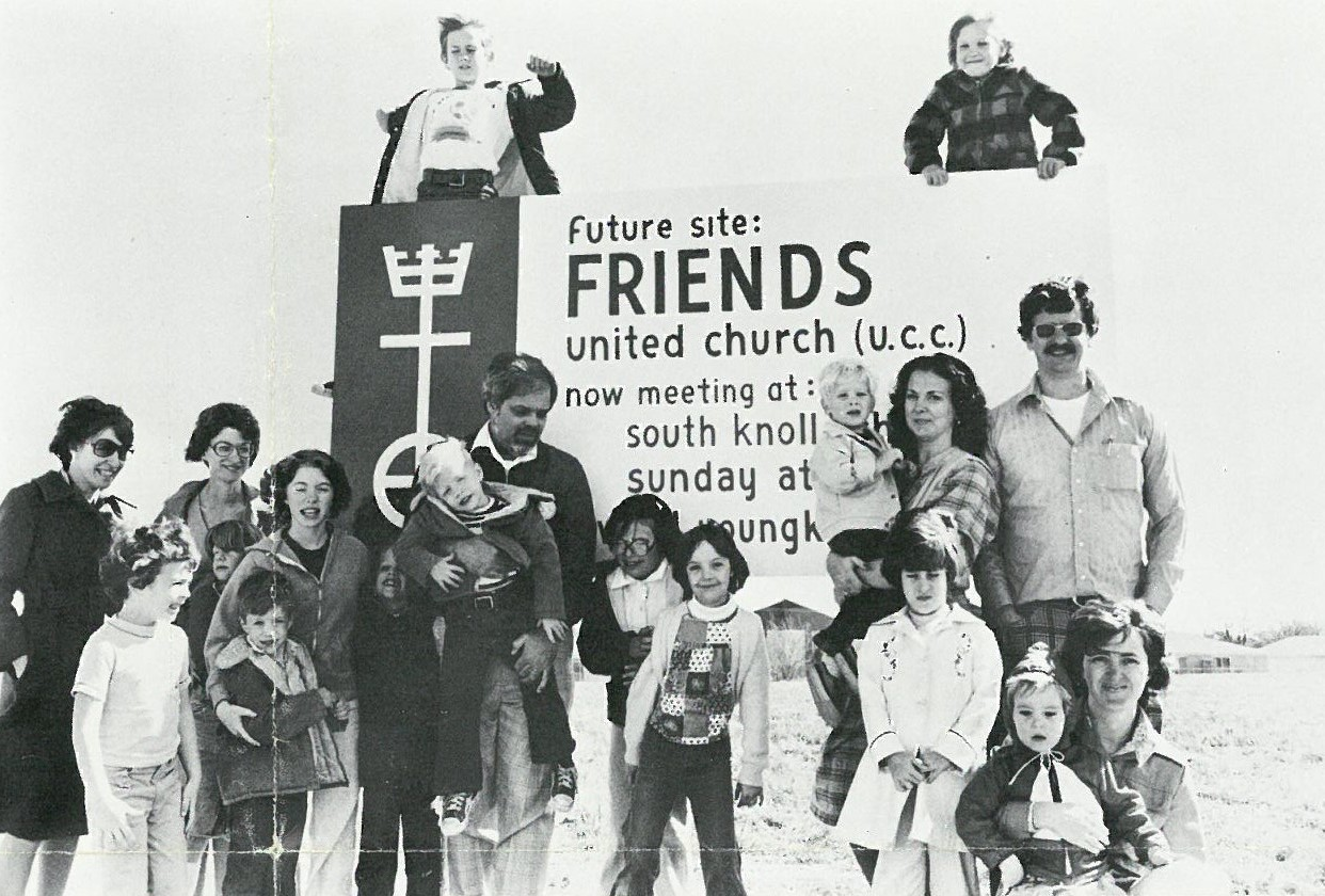 A black-and-white photo shows a dozen people, adults and children, posing with a large sign that rea