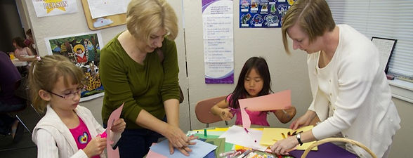 Two Sunday School teachers helping students with a craft