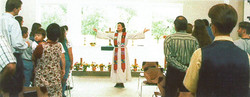 Arms outstretched, the pastor addresses her congregation.