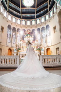 bride from back with beautiful trainceremony pictures at beautiful catholic church - Emma Males Photography