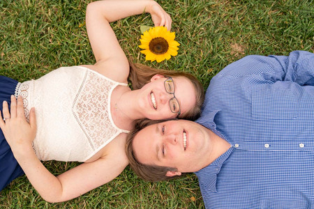 Couple laying on the ground with sunflower - Indianapolis Wedding Photographer