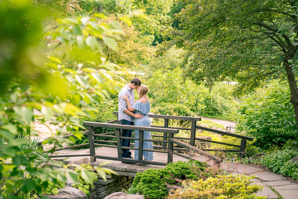 Indianapolis Indiana engagement session at Newfields gardens couple standing on a bridge