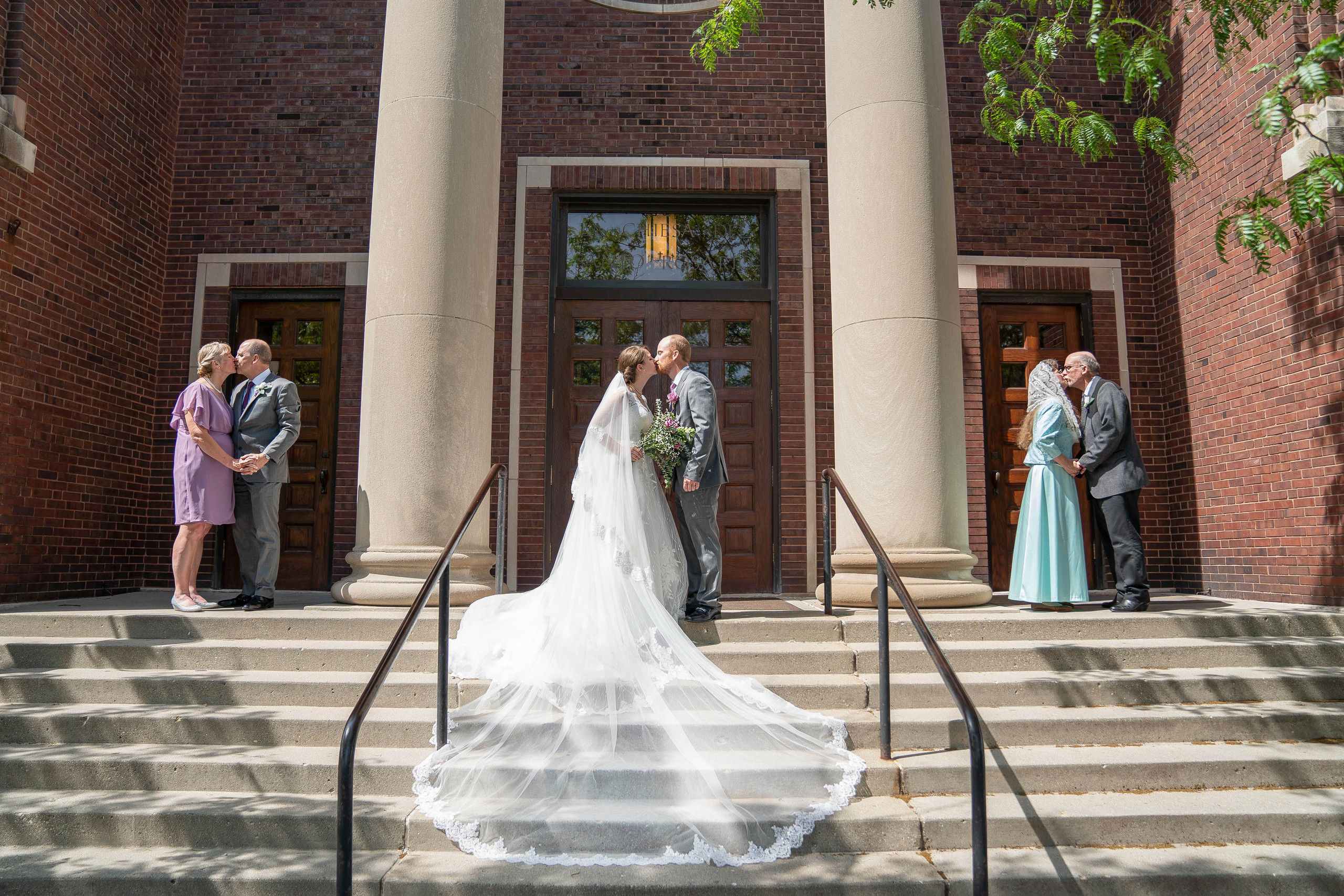 bride and groom kissing while parents kiss ceremony pictures at beautiful catholic church - Emma Males Photography