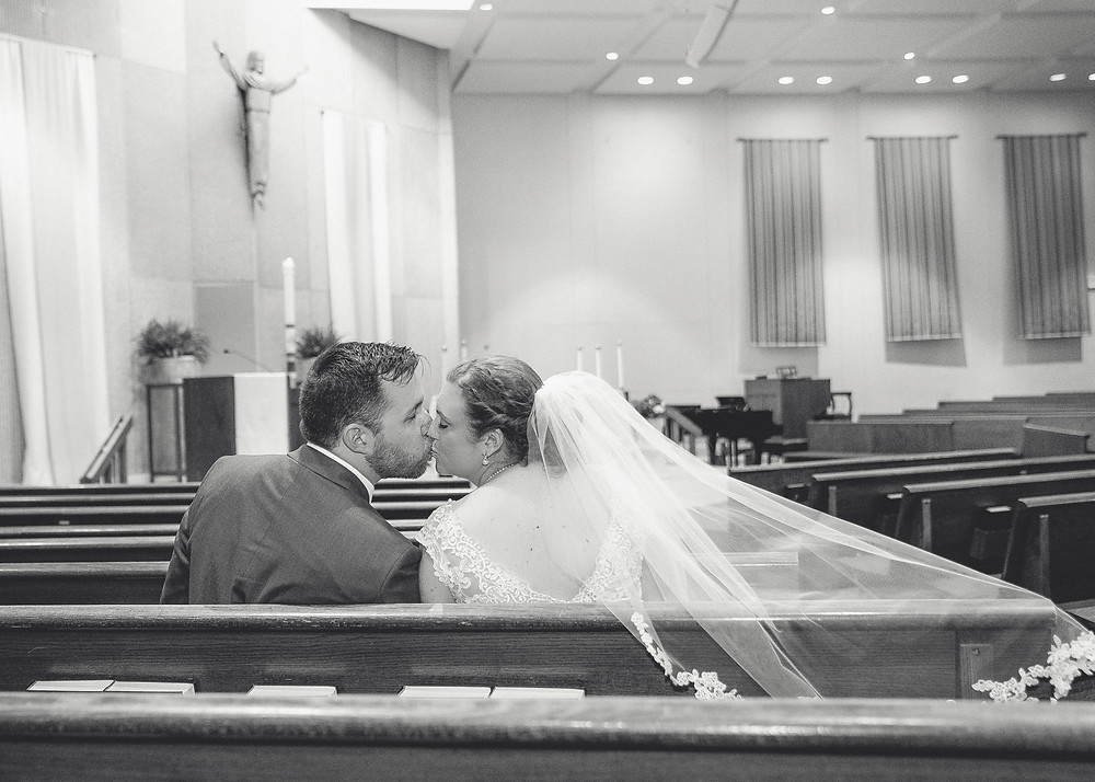 Indianapolis wedding bride and groom kissing in church