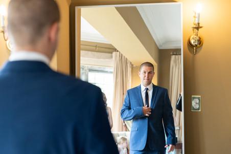 groom looking in the mirror