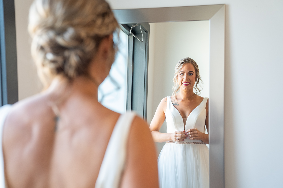 Bride seeing herself in mirror - www.emmamalesweddingphotography.com