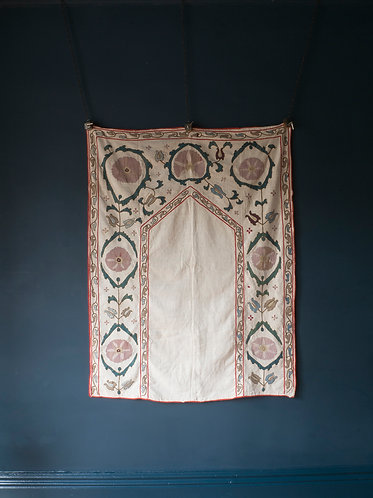 early 20th century prayer suzani. Pink and green silk embroidered floral elements on a plain cotton field with a red border