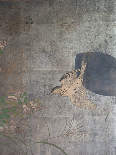 close up detail from a silver leaf byobu screen. A small bird in flight in front of an abstract black seed shape