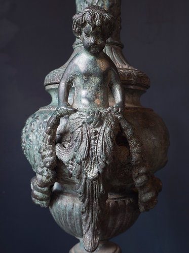 a cast bronze classical urn with putti at either side forming handles, heavily patinated and textured with green blue tones