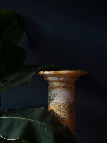 An antique, variegated alabaster pedestal column in tones of yellow orange and grey
