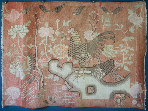 antique khotan samarkand pictorial rug. A cockerel on a rocky outcrop, the whole in pinks and apricot colours