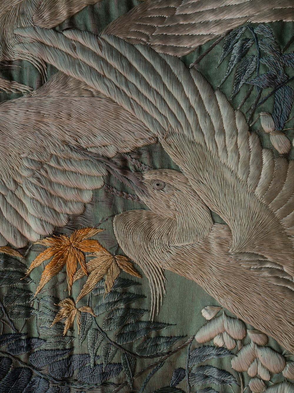 detail close up of the embroidery of a crane on a meiji period silk wall hanging