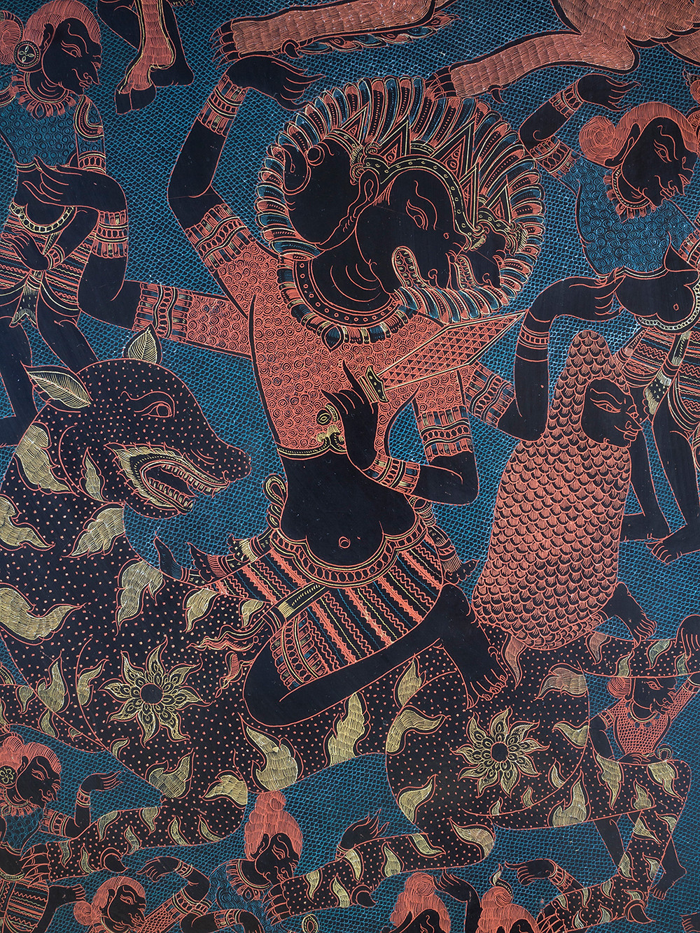 Close detail from a burmese lacquered engraved panel showing a 3 headed 4 armed god riding a tiger