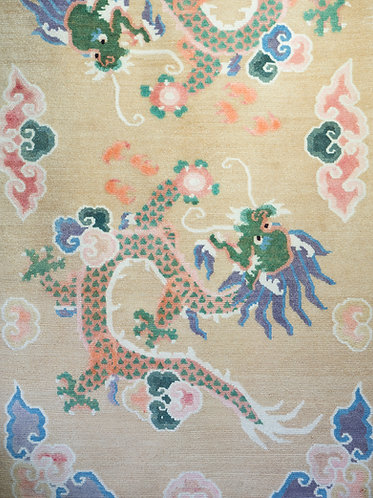 a tibetan rug in soft pastel colours featuring two dragons holding pearls among clouds