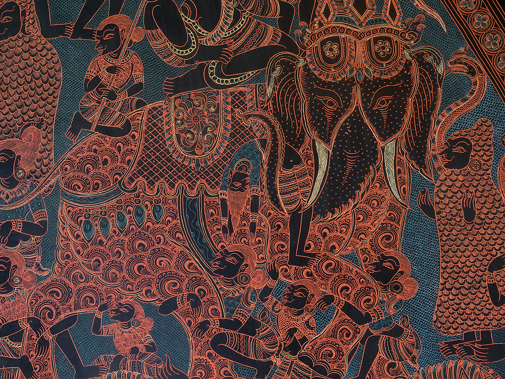 close up detail from a burmese engraving, showing figures draped around and over a painted elephant