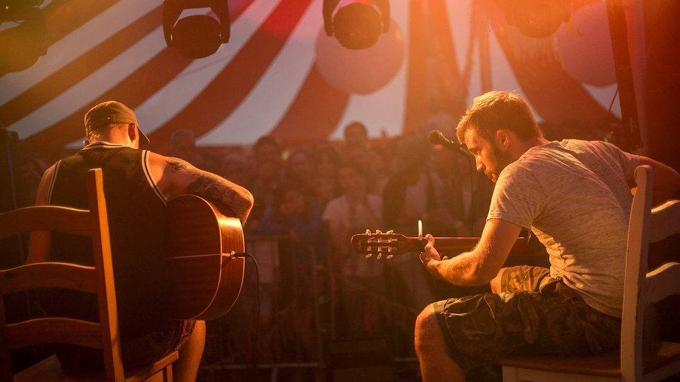 Two acoustic guitar players. Warm stage lighting glow.