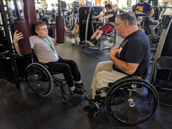A FLEX student in a wheelchair at a gym, getting exercise instructions from an adult in a wheelchair