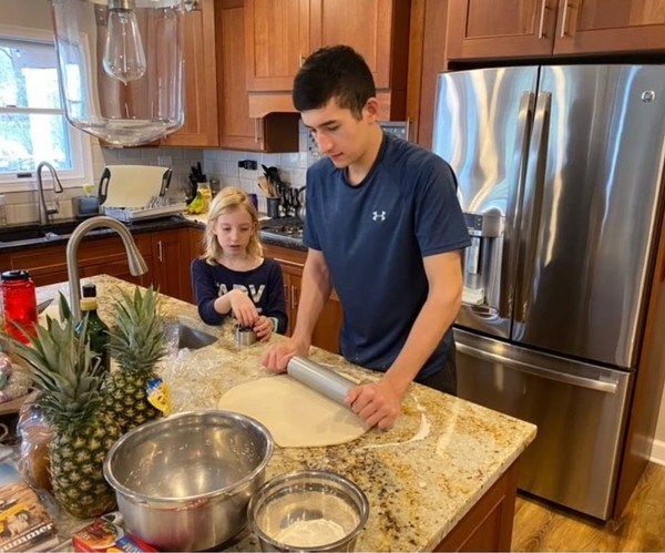 FLEX student cooking with his little host sister