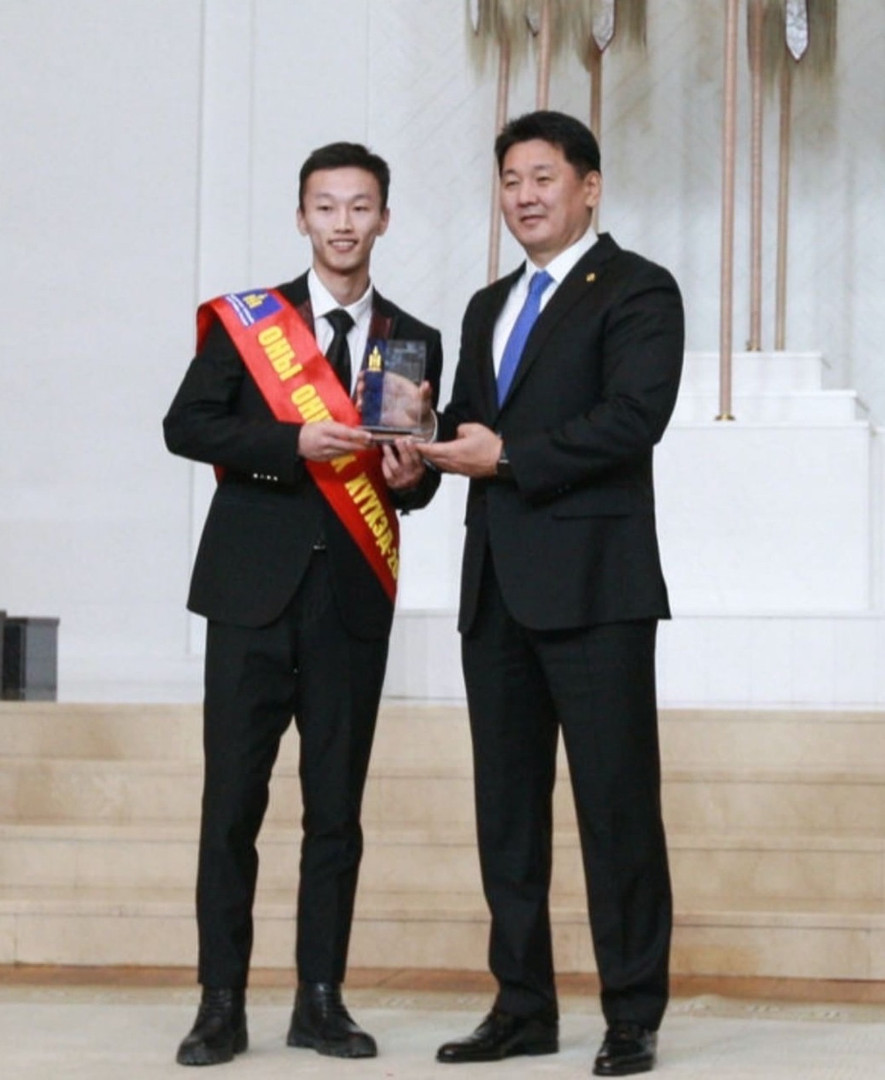 """A Mongolian alumnus accepting the """"Young Person of the Year"""" award from the Mongolian prime minister"""