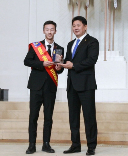 "A Mongolian alumnus accepting the ""Young Person of the Year"" award from the Mongolian prime minister"