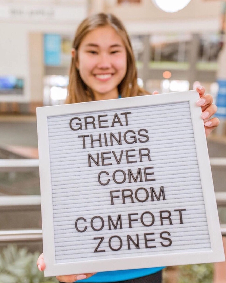 """FLEX student holding a sign that says """"Great Things Never Come From Comfort Zones"""""""