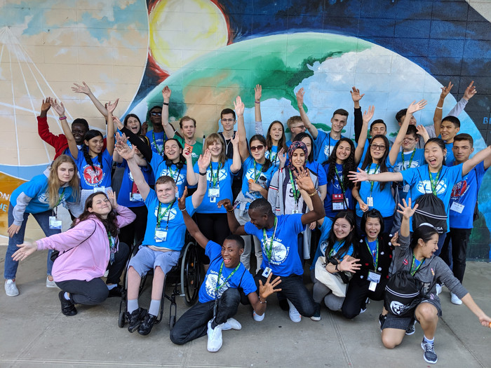 Large group of FLEX and YES students cheering in front of a large mural