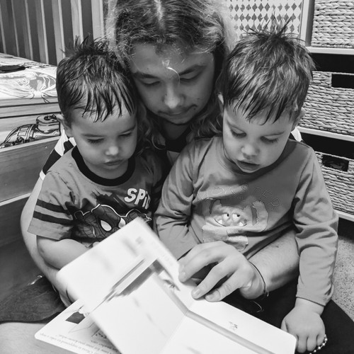 FLEX student reading a book with his two little host brothers in his lap