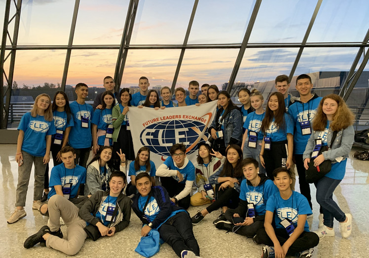 Large group of FLEX students posing around the FLEX flag at the airport