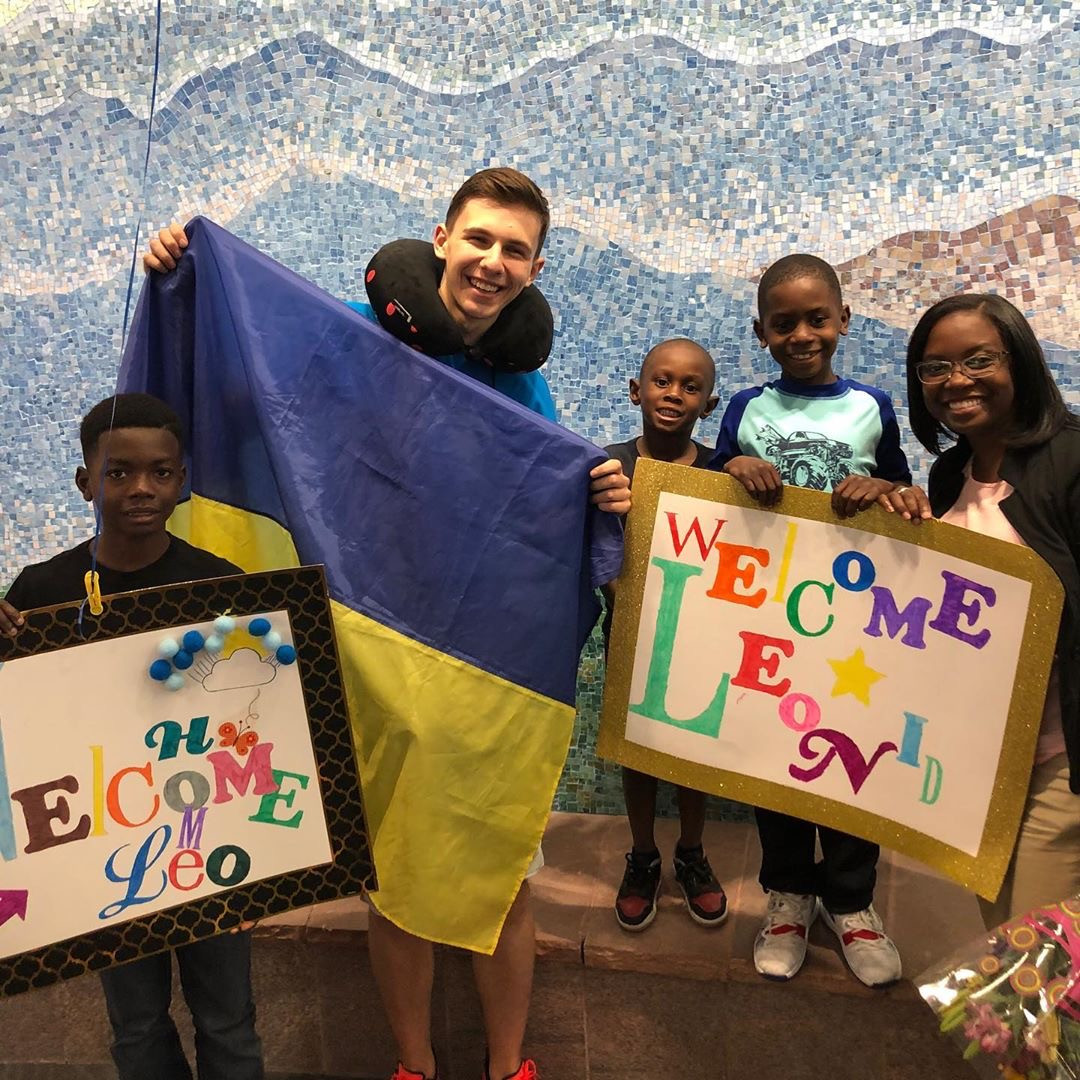 FLEX student greeted by his host family with Welcome signs.