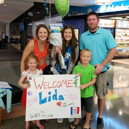 Host family welcomes their FLEX student with a poster, flowers, and balloons