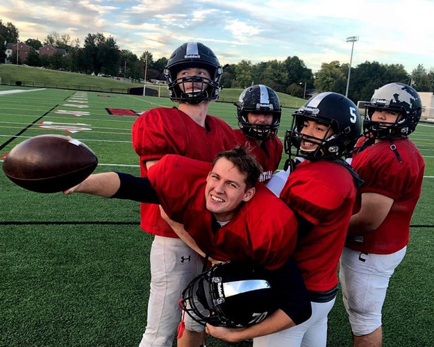FLEX student posing with an American football, with his football teammates lifting him up horizontally