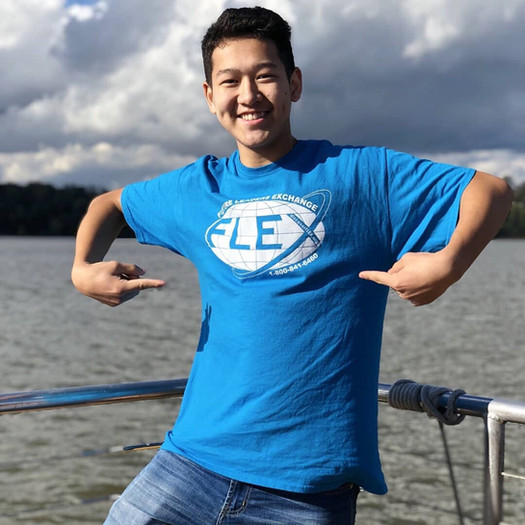 FLEX student smiling and pointing to the FLEX logo on his shirt