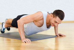 fitness, sport, training, gym and lifestyle concept - smiling man doing push-ups in the gym or at ho
