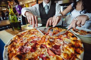 wedding pizza. bride and groom eat a big