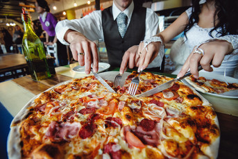 wedding pizza. bride and groom eat a big