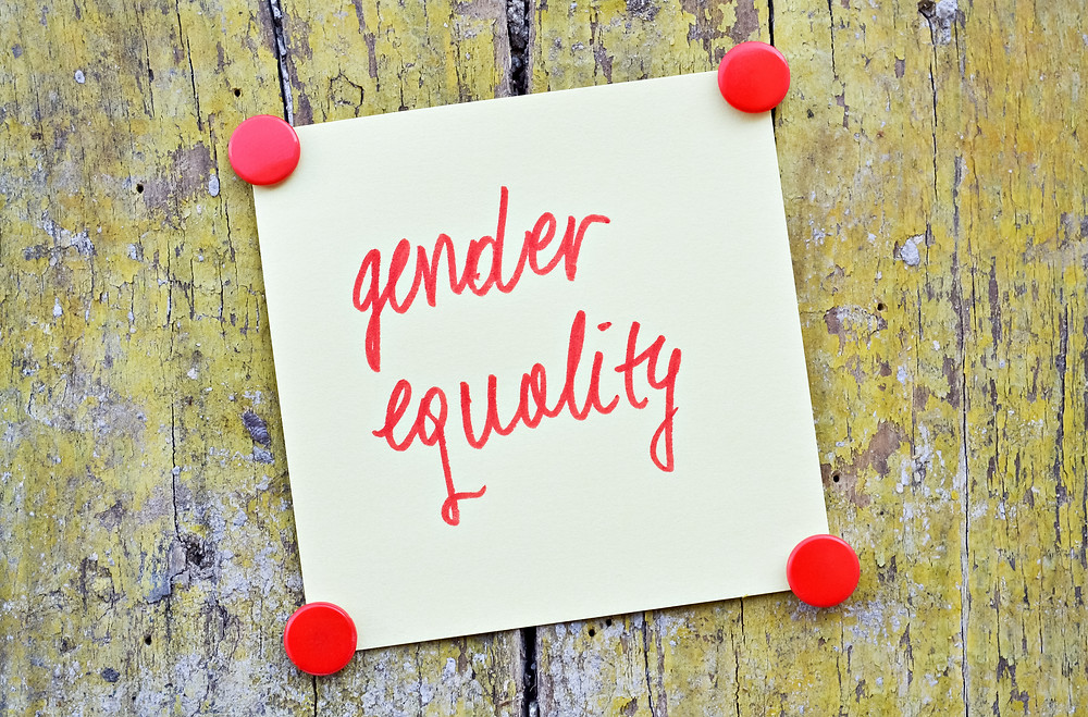 """Gender equality"" written in red ink on a piece of paper tacked to wood"