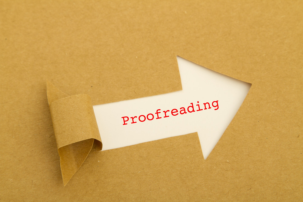 "The word ""proofreading"" typed in red on white paper"