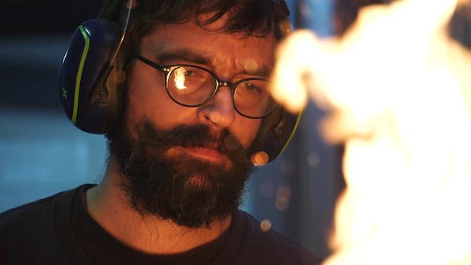 Un forgeron est en train de raviver un feu avant de commencer à forger. Les flammes reflètent sur ses lunettes. Il travaille pour l'entreprise La Forge de Style à Saint Macaire en Mauges. Cette images est tirée d'une vidéo pour le Réseau du Bellay réalisée par l'agence audiovisuelle Edito Prod.