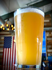 Pint glass of beer, with american flag behind it
