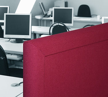 Burgundy free standing sound absorbing office divider with computers and desks in background