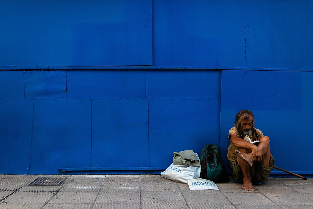 A homeless person sitting in sidewalk