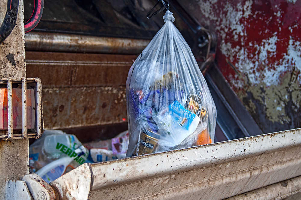 Trashes inside a plastic bag in a garbage truck